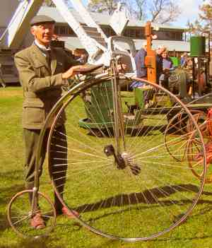 Photograph: Man posing with a penny farthing bicycle.